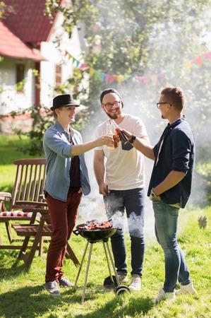 vrije tijd, voedsel, mensen, vriendschap en vakantie concept - gelukkige vrienden koken vlees op barbecue grill en drinken bier in de zomer buiten partij