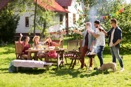 leisure, food, people, friendship and holidays concept - happy friends cooking meat on barbecue grill and drinking beer at summer outdoor party Banco de Imagens