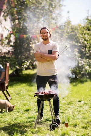 leisure, food, people and holidays concept - happy young man cooking meat on barbecue grill at outdoor summer party Stock Photo