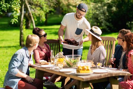vrije tijd, vakantie, eten, mensen en eten concept - gelukkige vrienden met vlees voor een diner in de zomer tuinfeest