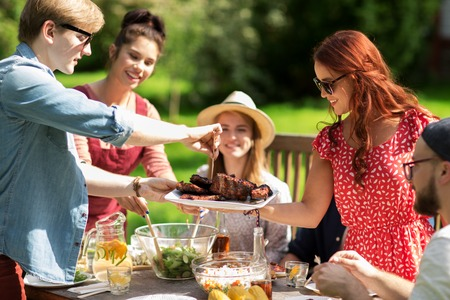 семья: отдых, праздники, еда, люди и концепции питания - счастливые друзья, мясо на ужин в летнем саду партии Фото со стока