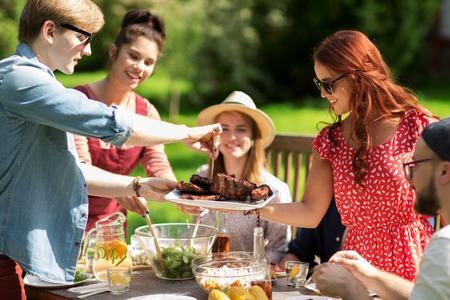 레저, 휴일, 먹고, 사람과 음식 개념 - 여름 정원 파티에서 저녁 식사를 위해 고기를 가진 행복 친구