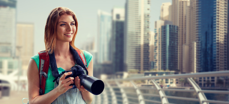 camera girl: adventure, travel, tourism, hike and people concept - happy young woman with backpack and camera photographing over dubai city waterfront background