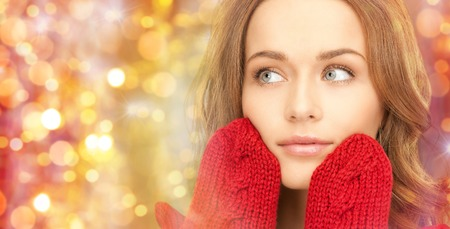beautiful face woman: winter, holidays, christmas and people concept - close up of happy young woman in red mittens touching her face over lights background