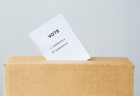 voting paper: voting and civil rights concept - vote with two candidates inserted into ballot box slot on election
