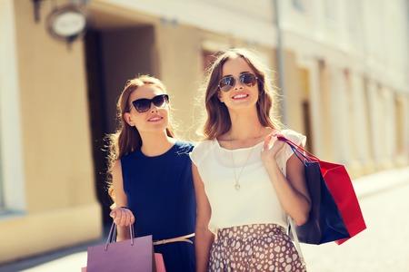 mujeres fashion: la venta, el consumo y el concepto de las personas - mujeres jóvenes felices con bolsas de compras caminando por la calle de la ciudad