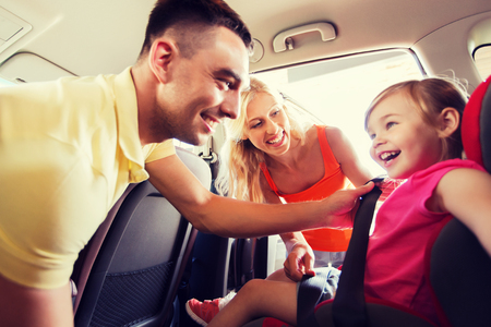 family, transport, road trip and people concept - happy parents fastening child with safety belt in baby car seat Stock Photo