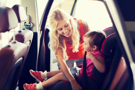 asiento: la familia, el transporte, la seguridad, viaje por carretera y la gente concepto - la madre feliz de fijación niño con el cinturón de seguridad del coche