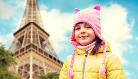 childhood, tourism, travel, vacation and people concept - happy beautiful little girl over eiffel tower in paris background Stock Photo