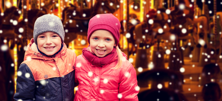 childhood,  holidays winter, christmas, friendship and people concept - happy little girl and boy over snow and carousel background Stock Photo