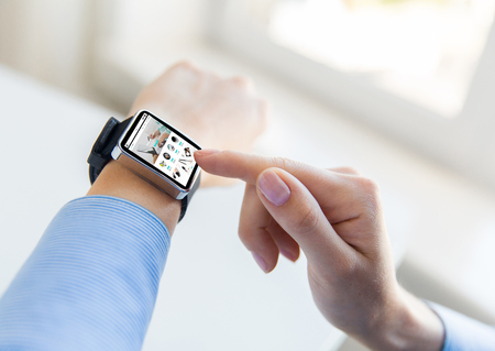 web directories: business, modern technology, internet shopping and people concept - close up of female hands setting smart watch with online shop on screen at office Stock Photo