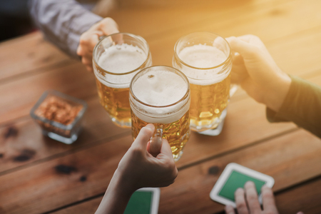 people, leisure and drinks concept - close up of hands clinking beer mugs at bar or pub Stock Photo