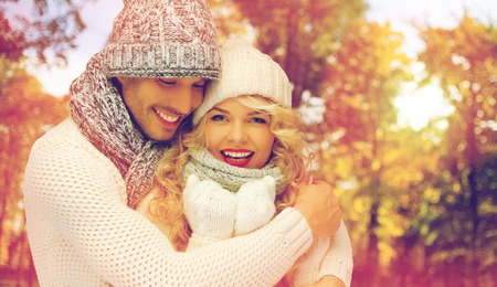 season, people, love and fashion concept - happy family couple in warm clothes over autumn background and sunlight