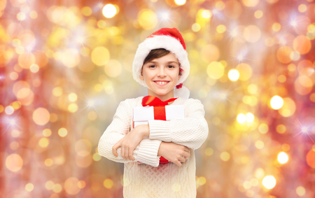 latin child: holidays, presents, christmas, childhood and people concept - smiling happy boy in santa hat with gift box over lights background Stock Photo