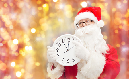 christmas, holidays and people concept - man in costume of santa claus with clock showing twelve pointing finger over lights background
