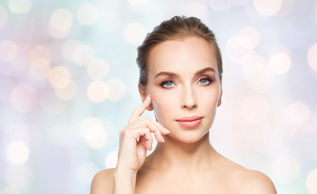 beauty, people and plastic surgery concept - beautiful young woman showing her cheekbone over blue holidays lights background Stock Photo