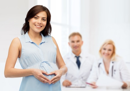 pregnancy, love, people, medicine and fertility concept - happy pregnant woman making heart gesture on belly over medics at maternity hospital background Banco de Imagens
