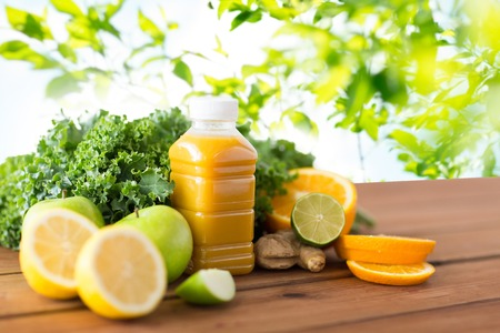 clean food: healthy eating, food, dieting and vegetarian concept - bottle with orange juice, fruits and vegetables on wooden table over green natural background