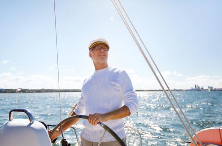 セーリング、年齢、観光、旅行、人々 の概念 - ステアリング ホイールと移動の帆ボートや海に浮かぶヨットのキャプテン ハットに幸せの年配の男