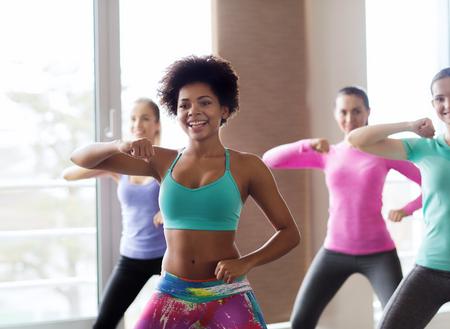 danza africana: fitness, deporte, la danza y el concepto de estilo de vida - grupo de gente sonriente con el entrenador bailando en el gimnasio o estudio Foto de archivo