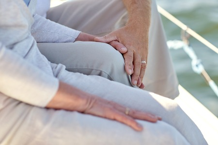 sailing, age, tourism, travel and people concept - close up of happy senior couple hugging and talking on sail boat or yacht deck floating in sea Reklamní fotografie