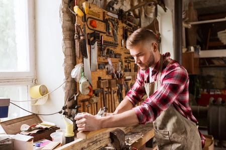 chippy: profession, carpentry, woodwork and people concept - carpenter working with plane and wood plank at workshop