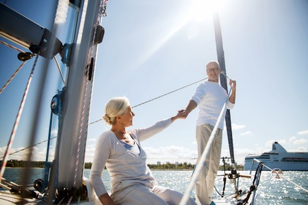 sailing, age, tourism, travel and people concept - happy senior couple holding hands on sail boat or yacht deck floating in sea Reklamní fotografie