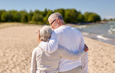 rear view: family, age, travel, tourism and people concept - happy senior couple hugging on summer beach
