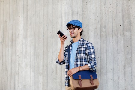 speaker phone: leisure, technology, communication and people concept - smiling hipster man with shoulder bag using voice command recorder or calling on smartphone at street wall