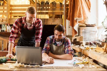 Profesión, carpintería, carpintería y concepto de la gente - dos carpinteros con el ordenador portátil y el modelo en el taller Foto de archivo - 64664713