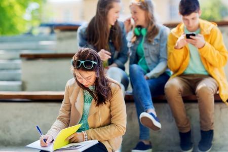 onderwijs, pesten, middelbare school, sociale relaties en mensen concept - ongelukkig student meisje met boek lijden van klasgenoten spot