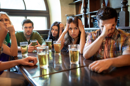 sports bar: people, leisure, friendship and entertainment concept - friends drinking beer and watching sport game or football match at bar or pub