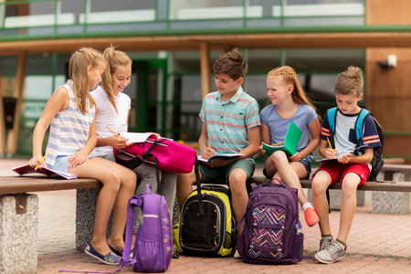 yard: primary education, friendship, childhood, communication and people concept - group of happy elementary school students with backpacks and notebooks sitting on bench outdoors Stock Photo