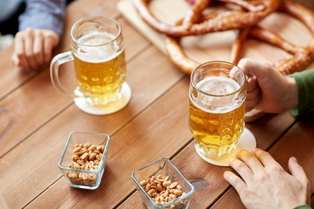 people, leisure and drinks concept - close up of male hands with beer mugs and pretzels at bar or pub Stock Photo