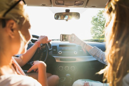 summer vacation, holidays, travel, road trip and people concept - happy teenage girls or young women with smartphone taking selfie in car