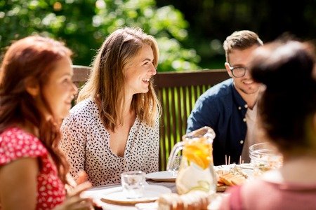 holiday gathering: leisure, holidays, eating, people and food concept - happy friends having dinner at summer garden party