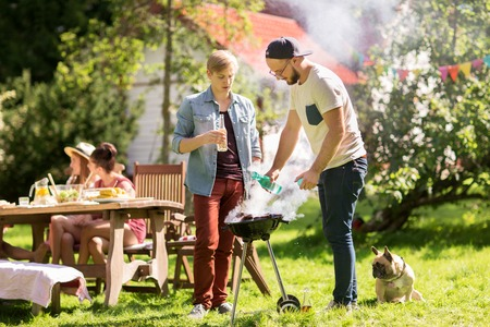 home cooking: leisure, food, people and holidays concept - friends cooking meat on barbecue grill at summer outdoor party Stock Photo