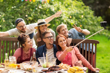 leisure, party, technology, people and holidays concept - happy friends taking picture with smartphone selfie stick and gathering for dinner at summer garden party Stock Photo