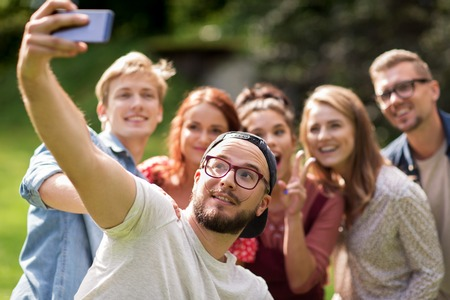 young group: leisure, holidays, reunion, people and friendship concept - happy teenage friends taking selfie by smartphone at summer