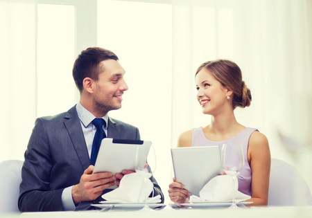 multiple choice: restaurant, couple, technology and holiday concept - smiling couple with menus on tablet pc computers at restaurant