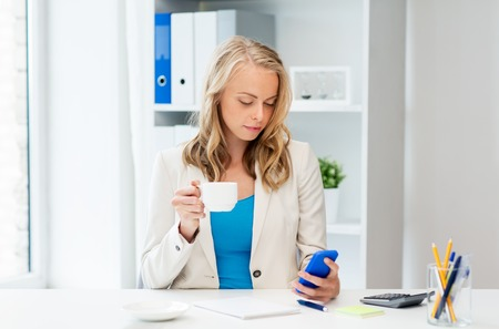 business, technology, people and communication concept - businesswoman texting on smartphone at office Stock Photo