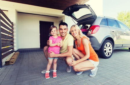 hatchback: transport, leisure, road trip and people concept - happy family with little girl and hatchback car at home parking space