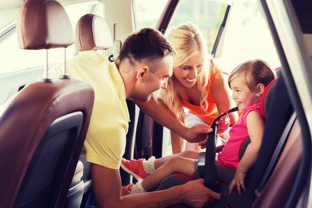 familie, vervoer, road trip en mensen concept - gelukkige ouders vastmaken kind met veiligheidsgordel in baby-autozitje Stockfoto