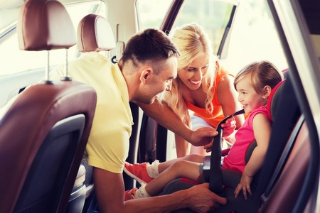 car seat: family, transport, road trip and people concept - happy parents fastening child with safety belt in baby car seat Stock Photo