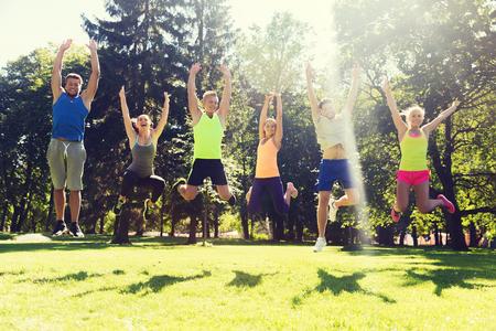 salud y deporte: fitness, deporte, la amistad y el concepto de estilo de vida saludable - grupo de amigos o deportistas adolescentes saltando feliz altos al aire libre