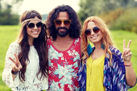 summer sign: nature, summer, youth culture, gesture and people concept - smiling young hippie friends in sunglasses showing peace hand sign on green field