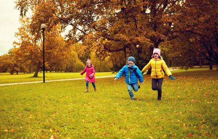 autumn, childhood, leisure and people concept - group of happy little kids playing tag game and running in park outdoors photo