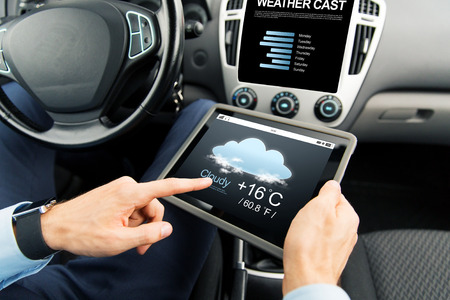 Transporte, viaje de negocios, la tecnología, el pronóstico y el concepto de la gente - cerca de las manos masculinas explotación Tablet PC con el tiempo emitido en la pantalla en el coche