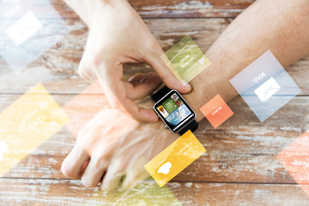 digital world: business, modern technology, media, internet and people concept - close up of male hands setting smart watch with news web page on screen on wooden table