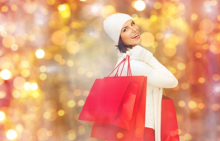 holidays, christmas, sale and people concept - happy young woman in winter clothes with shopping bags over lights background Stock Photo
